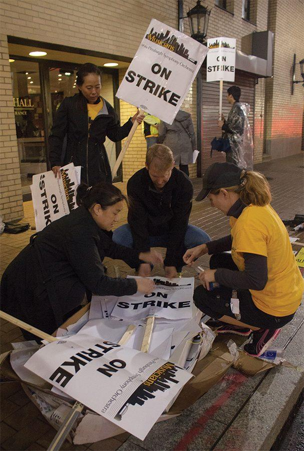 Pittsburgh+Symphony+musicians+Irene+Cheng%2C+Lisa+Gedris%2C+and+Charlie+Powers+making+picket+signs+while+striking+outside+of+Heinz+Hall+Sept.+30.