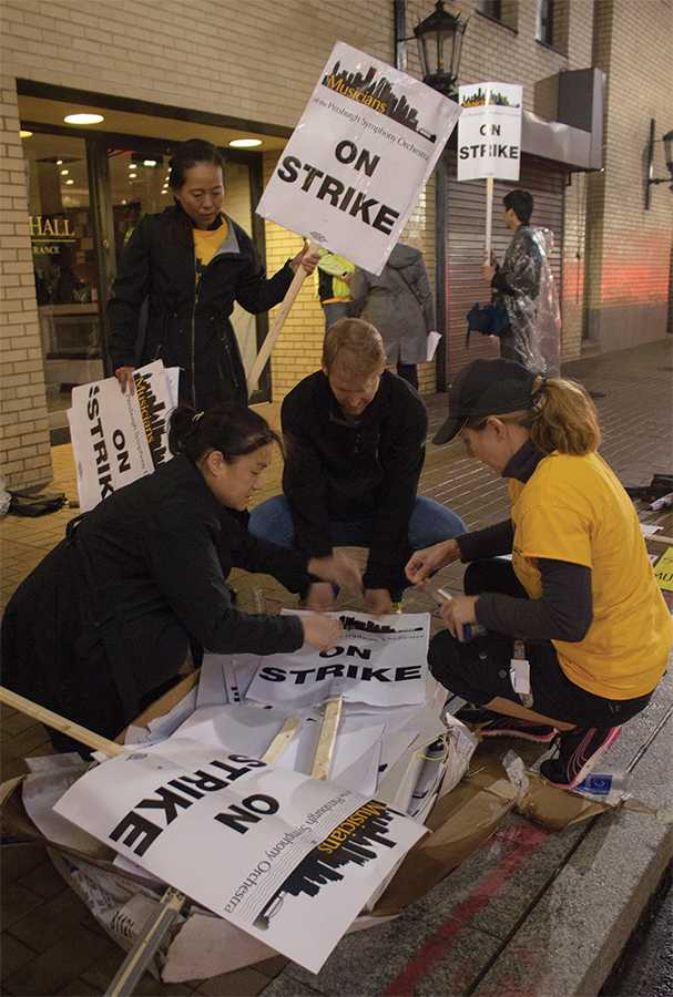 Pittsburgh Symphony musicians Irene Cheng, Lisa Gedris, and Charlie Powers making picket signs while striking outside of Heinz Hall Sept. 30.