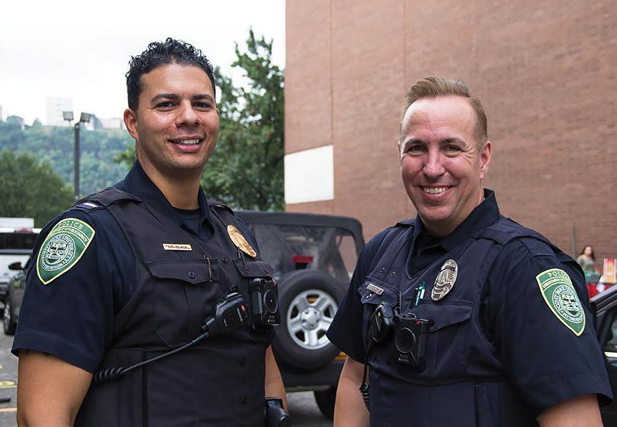Point Park police officers Lt. Nicholas Black and Alex Lee show off their body cameras on Move In Day, which they have worn since Aug 1. The newest requirement for officers is to carry a heroin OD antidote, Narcan.