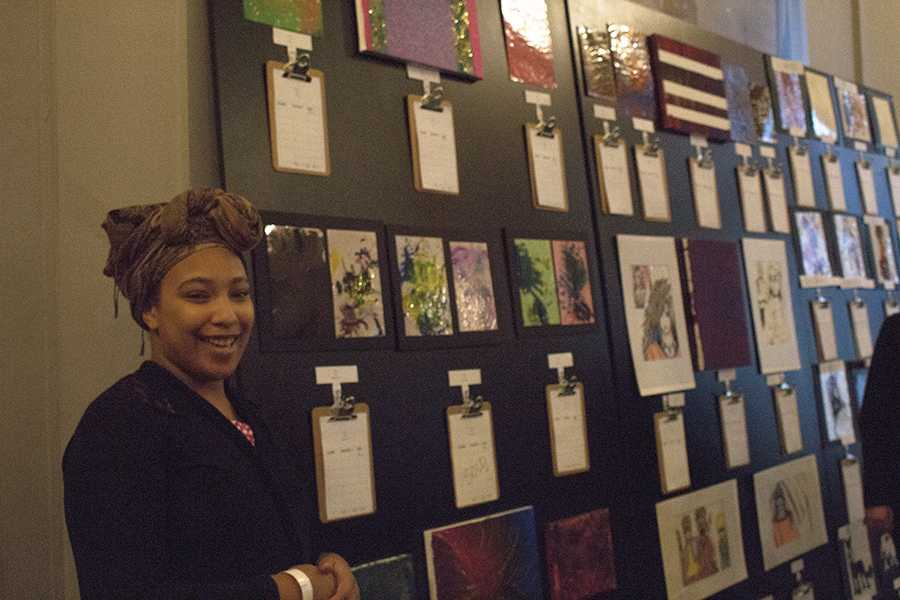 "Artist Tomika Torres explains the concept of change in her artwork at the ""We Live Here Too"" silent auction on Oct. 28."