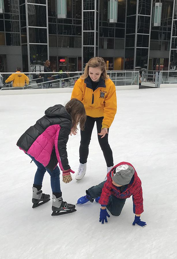 Julianna Rink, a sophomore dance major concentrating in jazz, helps skaters to their feet after a fall at the MassMutual Pittsburgh Ice Rink at PPG Place PPG Rink, where she is a skate guard.