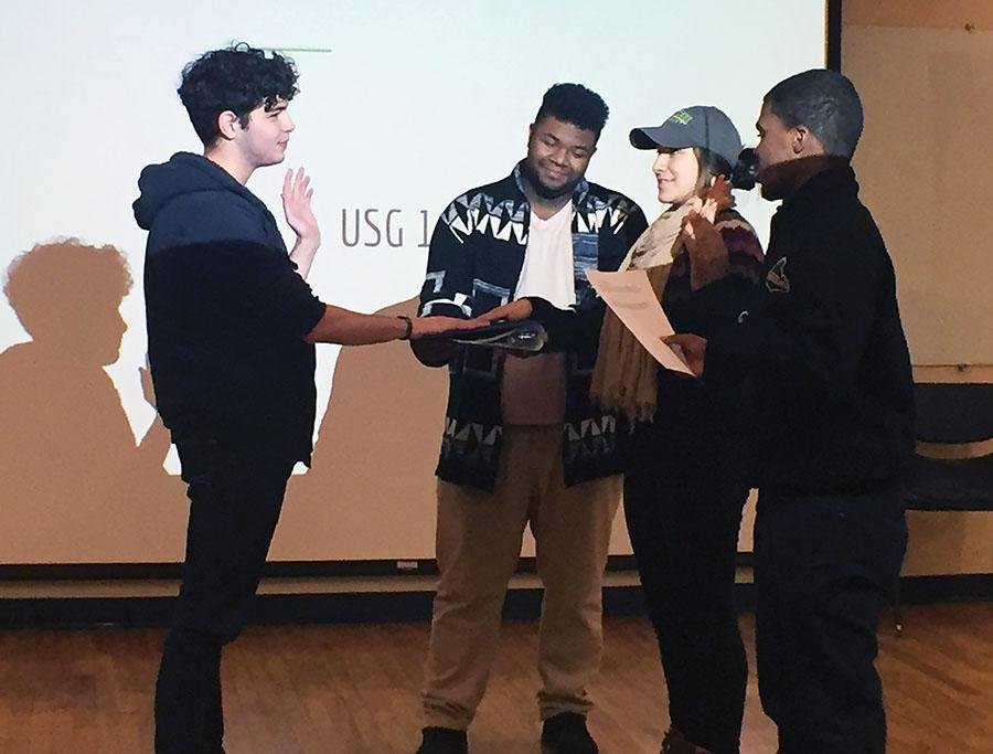 United Student Government President Blaine King, far right assisted by Parliamentarian Charles Murria, second from the left, swears in sophomore broadcasting major Samiar Nefzi and senior sports, arts and entertainment management major Priscilla Nevarez into student government.