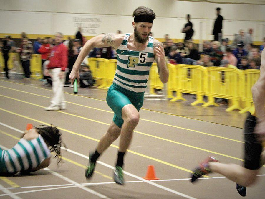 Aaron+Barlow%2C+sophomore%2C+runs+with+the+relay+stick+on+Friday%E2%80%99s+meet.+The+men%E2%80%99s+indoor+track+and+field+team+placed+1st+of+14+teams+that+participated+in+the+meet.%0A