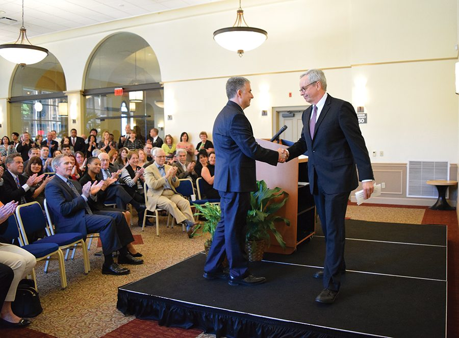 Provost John Pearson shakes hands with the newly appointed Rowland School of Business Dean, Steve Tanzilli, on Tuesday.
