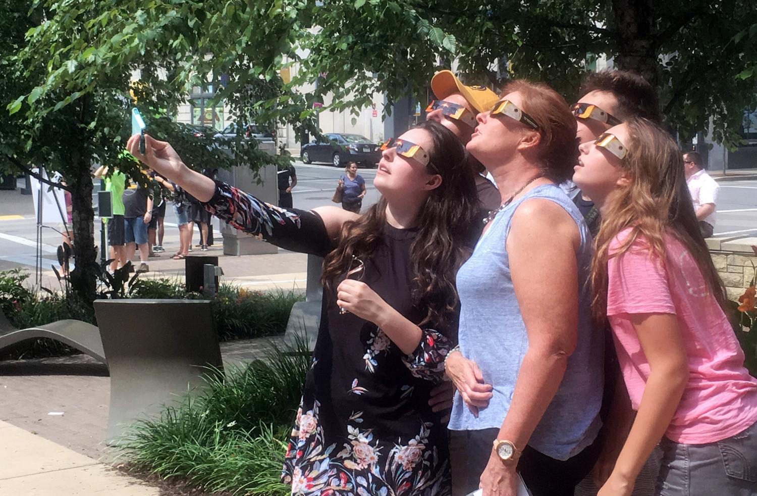 Freshman musical theatre major Frankie Seratch views the partial solar eclipse with his family during honors early move-in day on Aug. 21.