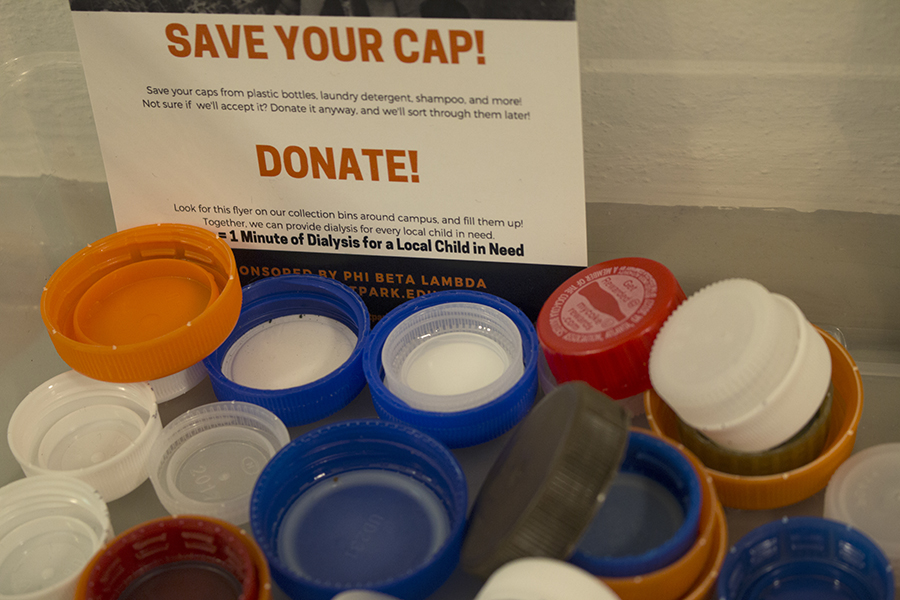 Caps for kids donation bins can commonly be found near recycling bins on campus