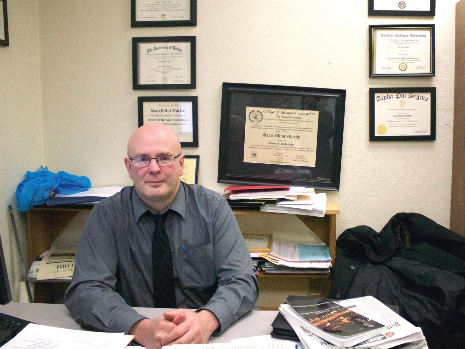 Dr. Martin, pictured here in his office, sits surrounded by his various degrees and awards.
