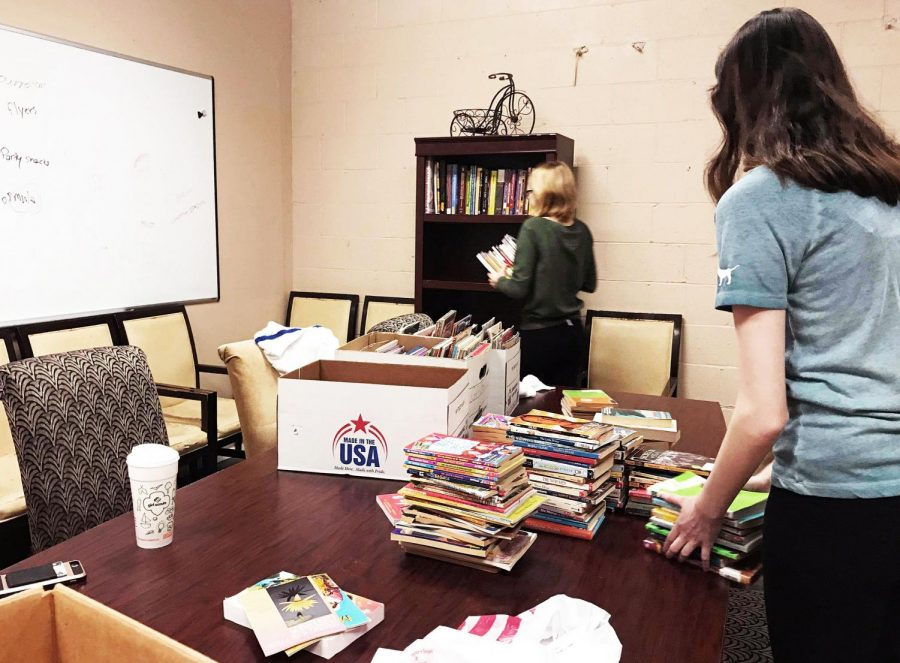 Freshman+honors+students+Madison+Kelkis+and+Angela+Runsack+organize+books+for+local+organization+A+Giving+Heart+as+part+of+Pioneer+Community+Day%2C+which+took+place+this+Saturday.+
