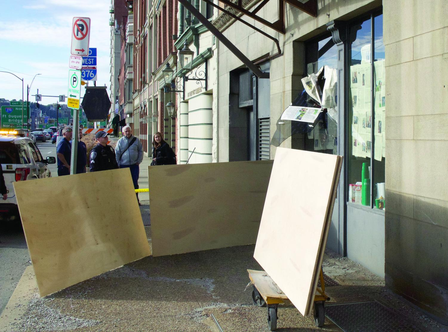Gracey Evans | The Globe An outward-facing window in the Globe and WPPJ office began cracking around 3 p.m. on Monday while students were inside the offices. Public safety responded to the situation immediately, and the window was pushed from the inside out onto the sidewalk of Fort Pitt Boulevard. Plywood is now temporarily covering the opening, and according to an engineer for the university, it is undetermined as to when the window will be repaired. This is due to the glass company having to special order the tempered glass.