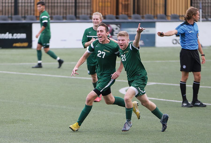 Freshman Christopher Ciucanu (left) celebrates his overtime goal with sophomore Mitchell Roell (right) Saturday at Highmark Stadium. The men's soccer team defeated Asbury 1-0 on their senior day.