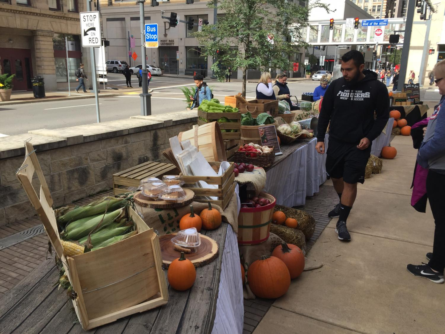 Junior Niko Roros strolls along the farmer's market-style selection during AppleFest. The event was put on by CulinArt and featured live music, fall-themed favors and plenty of pumpkins and apples.