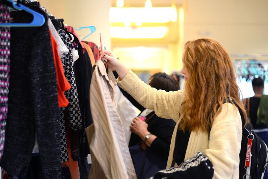 Freshman dance major Anna Fairbank sifts through clothes at Point Closet's first pop-up shop of the year.