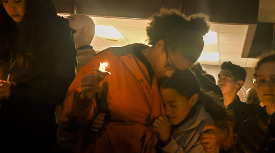 Isabel Smith exchanges an embrace during the vigil for the victims of the Tree of Life shooting Saturday night. Smith, alongside other high school students, organized the impromptu vigil.