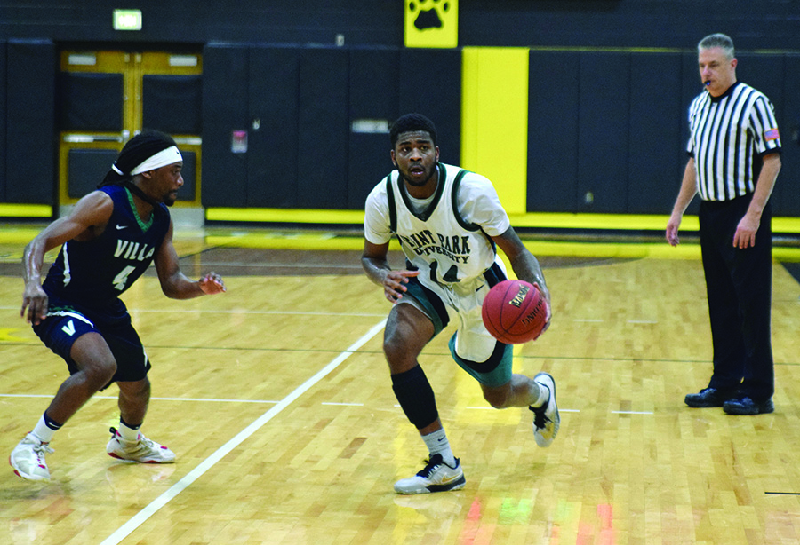 Senior guard Asim Pleas takes the ball in the offensive zone during a 2017 contest. The team dropped three games over Thanksgiving break.