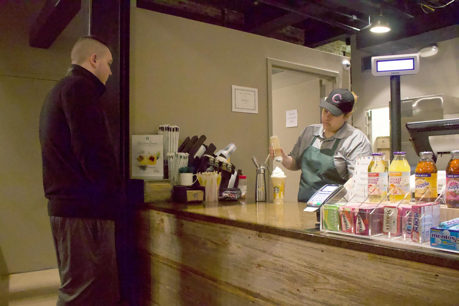 Freshman Brandon Bruce watches as a barista at Point Perk finishes preparing his coffee.