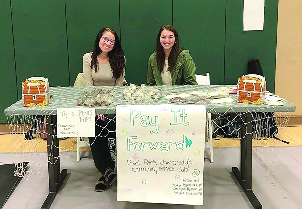 Pay It Forward's Treasurer Nicole Lakovic (left) and President Jillian Svonavec (right) run a table at the Spring 2018 Condom Carnival. Pay It Forward is one of a number of charitable campus clubs.