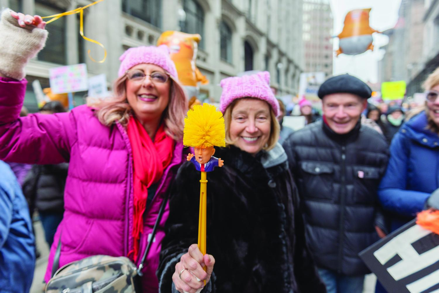 Women's March participants travel down Grant Street as one attendee proudly displays a toilet brush containing the likeness of President Donald Trump.