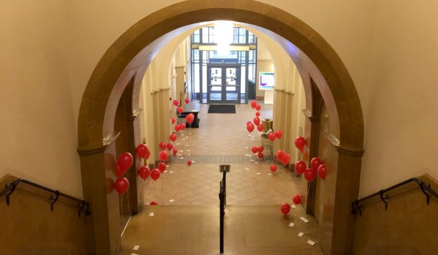 The+lobby+of+Lawrence+Hall+was+filled+with+red+balloons+donning+positive+messages+on+a+notecard+attached+to+their+strings.+The+university+Twitter+account+encouraged+students+to+%22spread+the+love%22+by+passing+along+the+balloons.