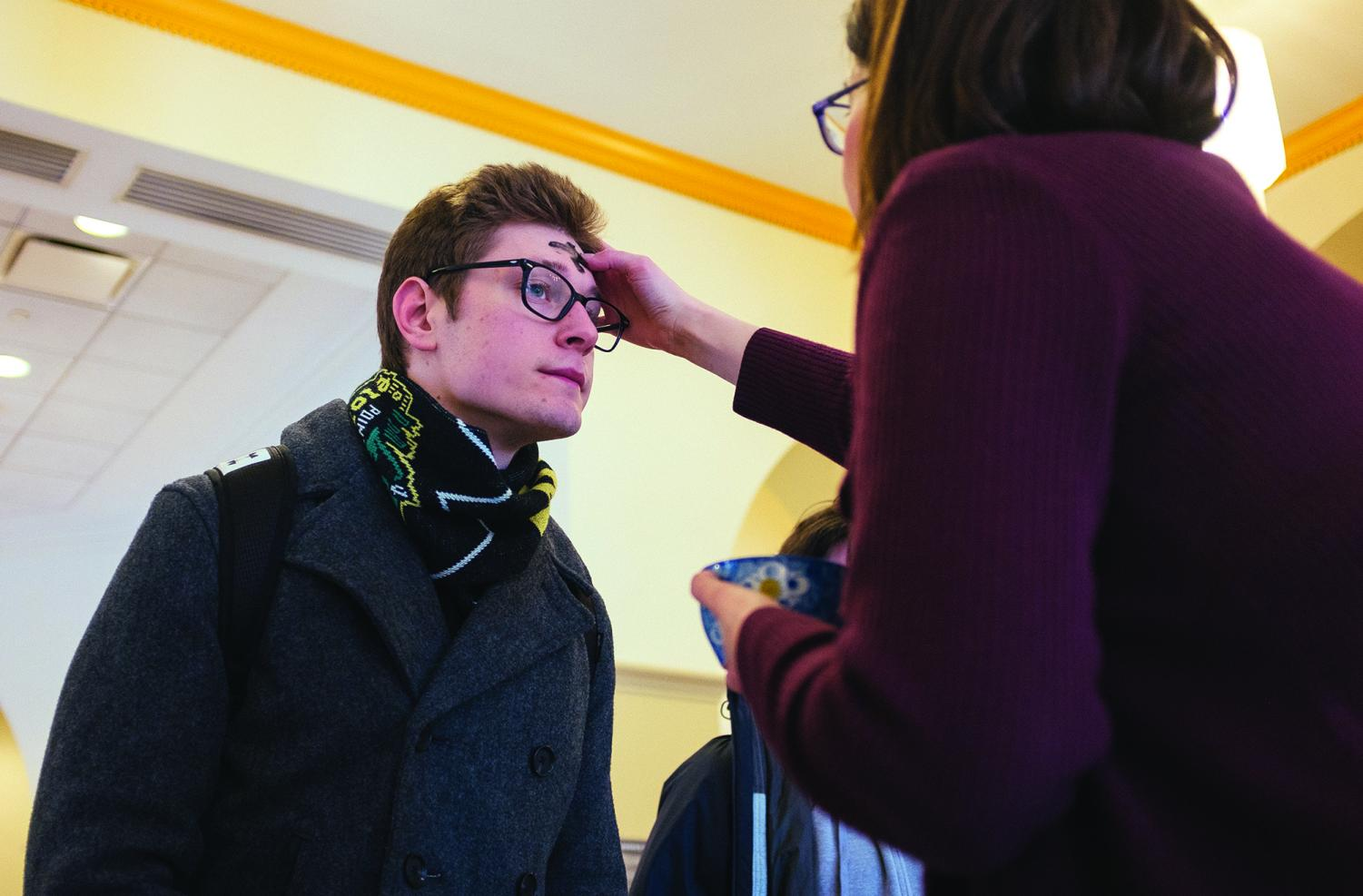 Nick Poprocky, senior public relations major, receives ashes for Ash Wednesday, the start of Lent, in the Lawrence Hall lobby from Pastor Jennifer McCurry.