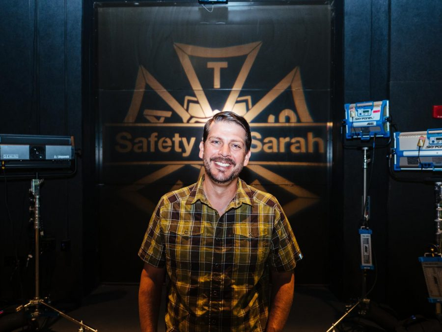 Cinema Safety Coordinator Terry Shirk poses in front of a Safety for Sarah light that shines on a wall in the soundstage of the Playhouse.