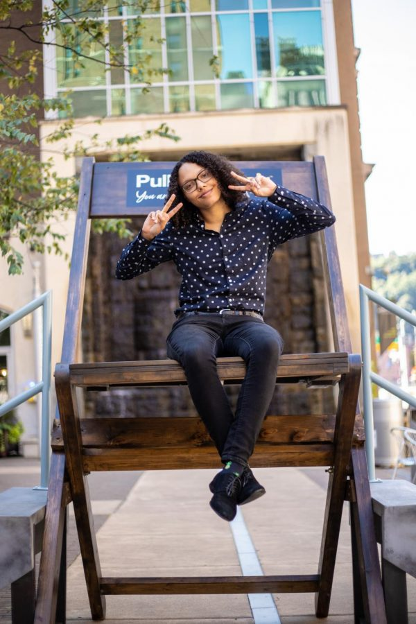 Marcyssa Brown, a senior SAEM major, sits on top of VistPittsburgh's 8-foot-tall chair at Village Park. VisitPittsburgh's Pull Up a Chair intiative came to campus last Wednesday.