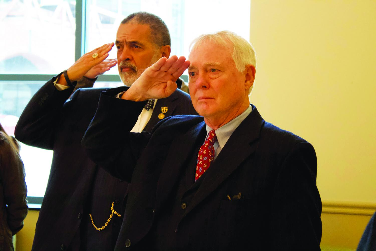 Dr. Gregory Rogers (left) and Dr. George Bromall (right) salute to the American flag as the National Anthem plays during a Veteran's Day service in LH Lobby on Nov. 11.