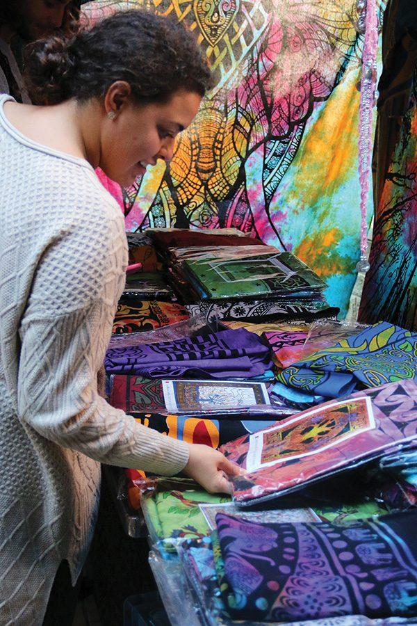 Gabby+De+Lima%2C+senior+business+major%2C+browses+the+selection+of+tapestries+for+sale+in+Village+Park+on+Wednesday%2C+October+12.