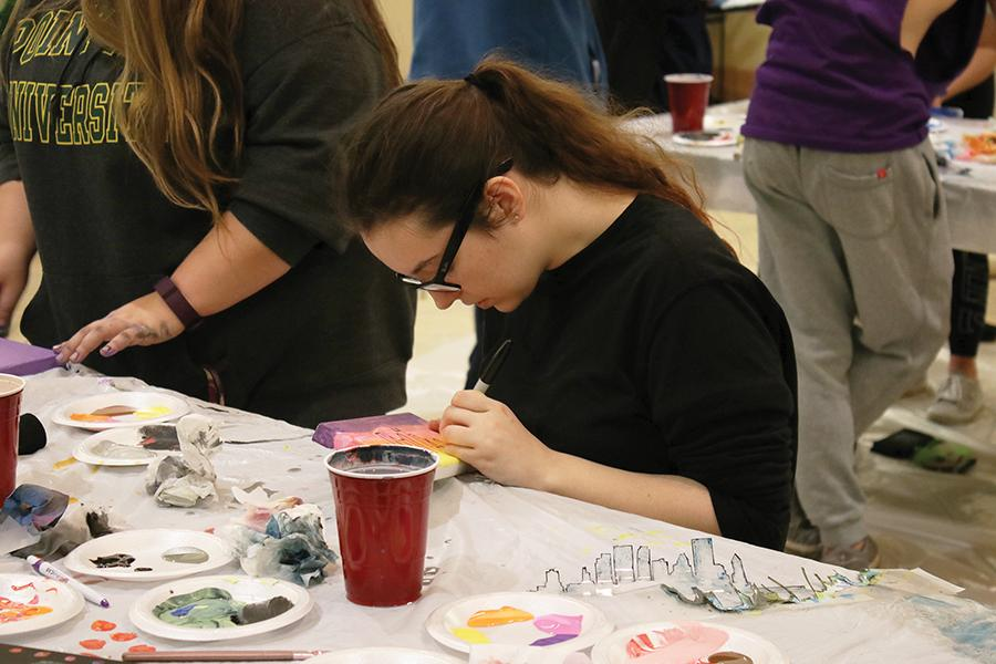 """Freshman theater arts major, Sarah Carson, paints at one of the tables in the Lawrence Hall lobby during the """"Paint the City"""" event Thursday night. CAB provided painting supplies along and an outline of the Pittsburgh skyline along with canvases for students to decorate."""