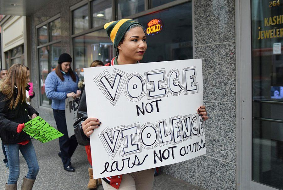 Jakirah Morrison, freshman undecided, walks in a silent protest around Point Park's campus and surrounding areas such as Market Square and PPG Place on Monday with other students and faculty members. This was one of the few events going on to observe Martin Luther King Jr. Day.