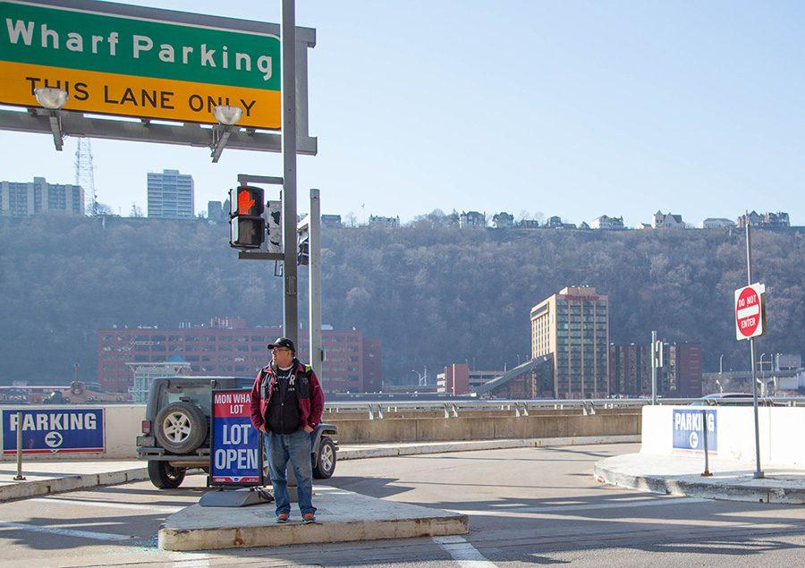 A pedestrian waits to cross road over Mon Wharf parking on Monday.