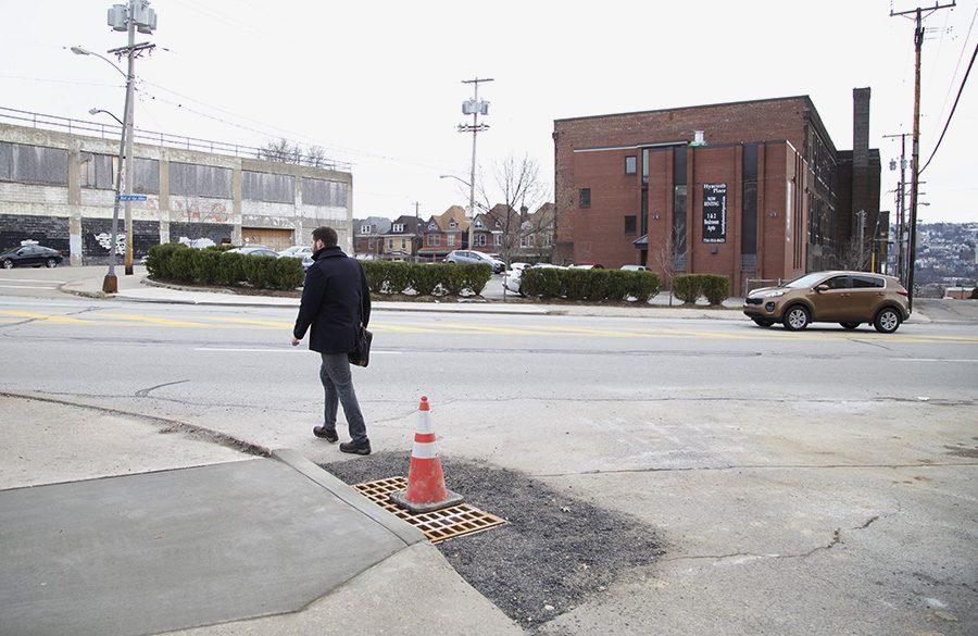 A traffic cone warns motorists of the fixed sinkhole on Hamlet Avenue in Oakland near the drop off point for Point Park shuttles at the Pittsburgh Playhouse Monday afternoon.