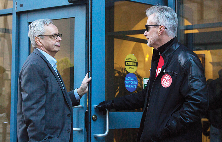 Rick Hawkins, artist in residence, holds door open for Provost John Pearson during the full time faculty union demonstration that he took part in on admitted students day Saturday.