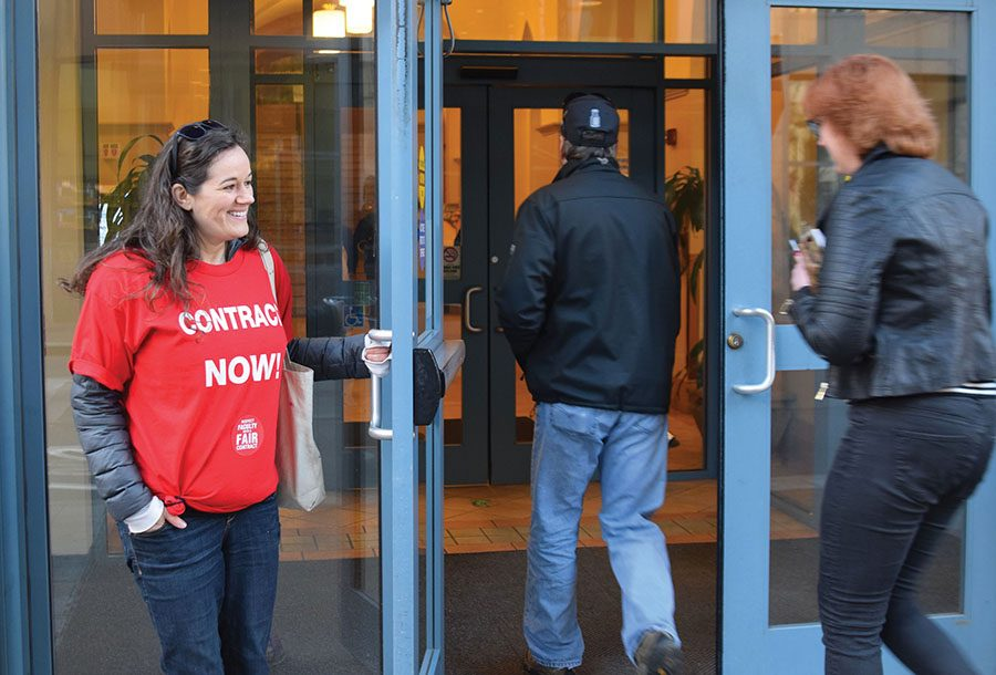April Friges, assistant professor of photography and program coordinator, holds door open for attendees of admitted students day during the full time faculty union demonstration that she took part in Saturday.