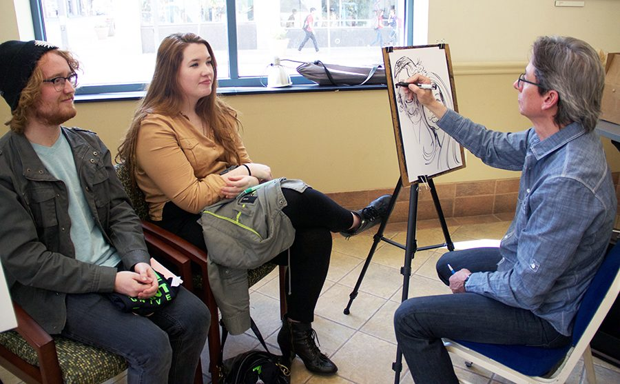 Andrew Miles, senior broadcast production major and Shannon Felletter, senior acting major, pose for a caricature in celebration of Point Park's Senior Week which started Monday.