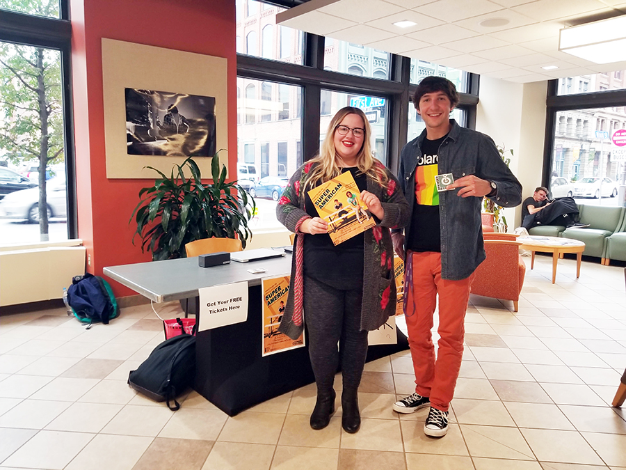 Kylie Koch and Chase Barron give out tickets in the West Penn lobby Thursday for an upcoming show at the Pittsburgh Playhouse featuring Super American, Young Lungs, and Chase and the Barons.