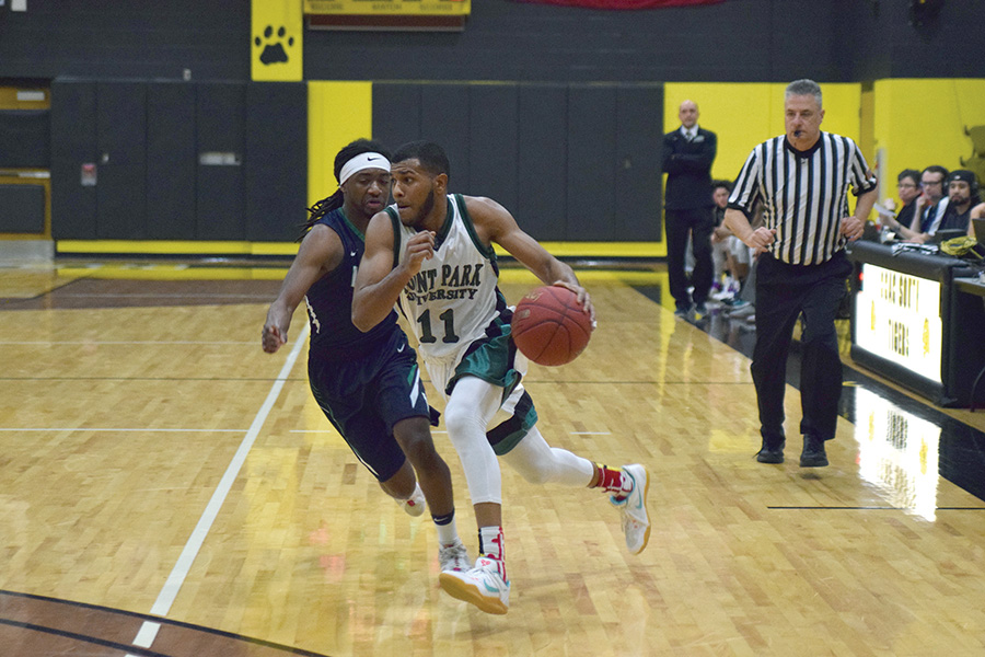 Senior point guard Gavin Rajahpillay drives the ball up the court past an opposing guard during a game against Villa Maria last year.