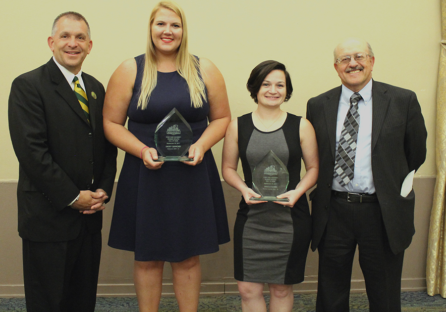 Dean of Students and Vice President of Student Affairs Keith Paylo, former women's volleyball player Lindsey Oberacker, former women's soccer player Angela Olivieri and Athletic Director Dan Swalga pose for a photo after the Pioneer Athletic Hall of Fame Induction Ceremony on Saturday in the Lawrence Hall Ballroom.