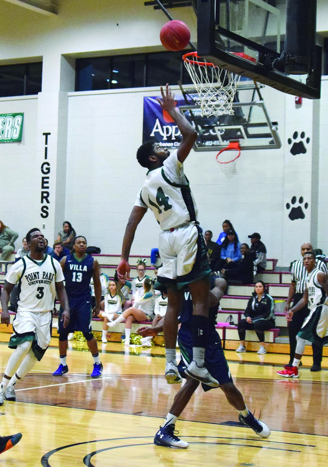 Junior guard Asim Pleas attempts a layup in a game against Villa Maria last season. The men won their season opener on Oct. 31 against Wilberforce.