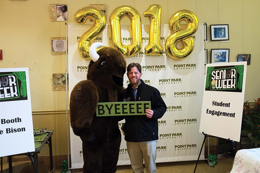 Michael Gieseke, Dean of Student Life, posing with Black Diamond II the Bison during the Senior Week Kick-Off in the Lawrence Hall Lobby on April 9, 2018.