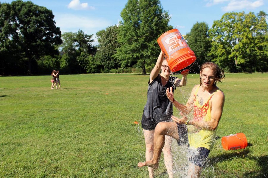 Senior biology major Alexandra Levi dumps a bucket of water on junior global cultural studies major Dylan Kersten. The event took place at Point State Park and drew a crowd of about 20 people.