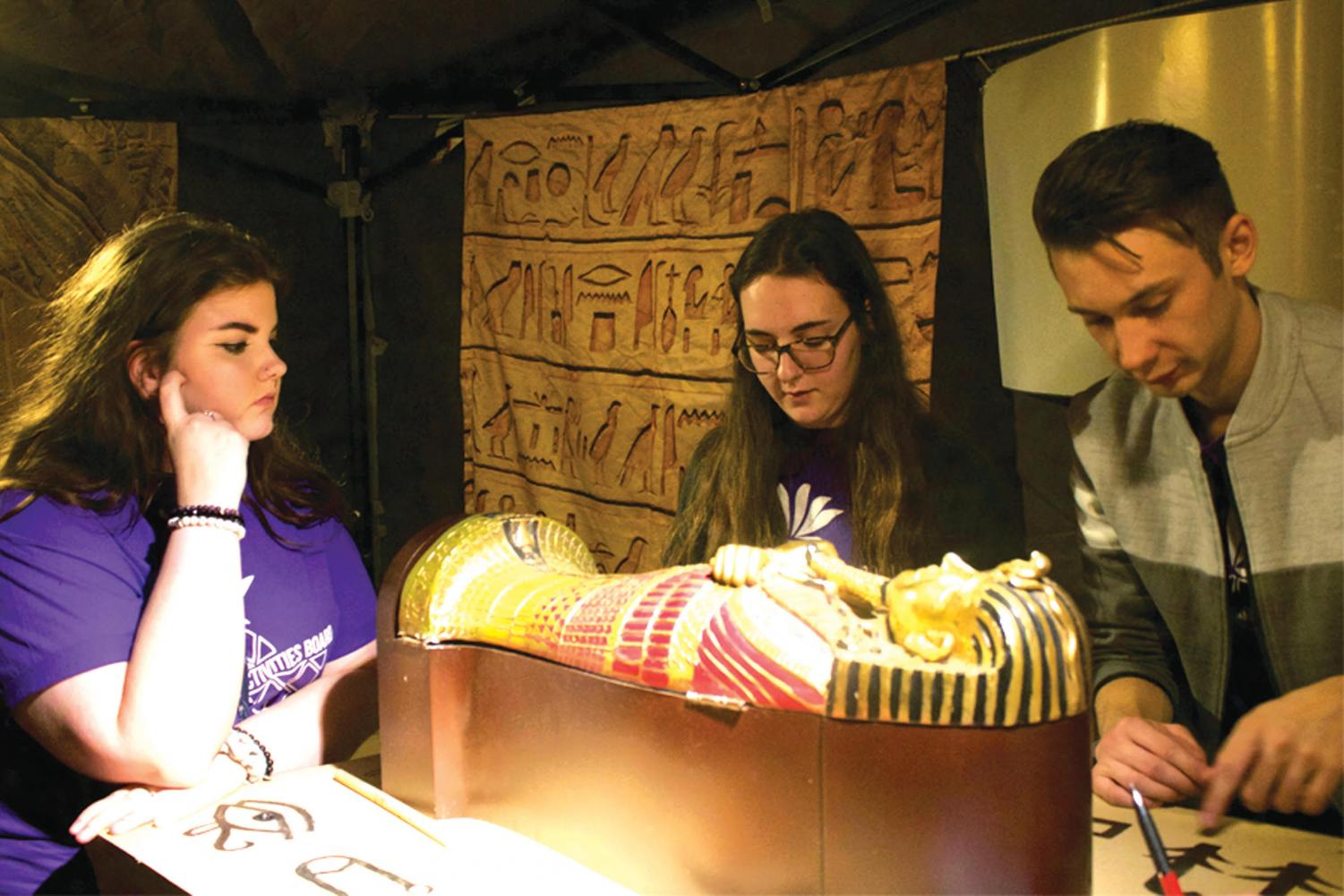 Freshman Emily Porter, sophomore Madeline Rexroad and junior Jake Taylor to try to decipher hieroglyphics in an Ancient Egyptian-themed escape room at CAB's event Saturday night.