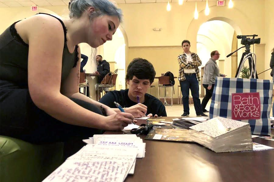 Grace Johns and Justin McGranahan, vice president and treasurer of Campus Cursive, respectively, work on writing their letters to the Squirel Hill community following the shooting.