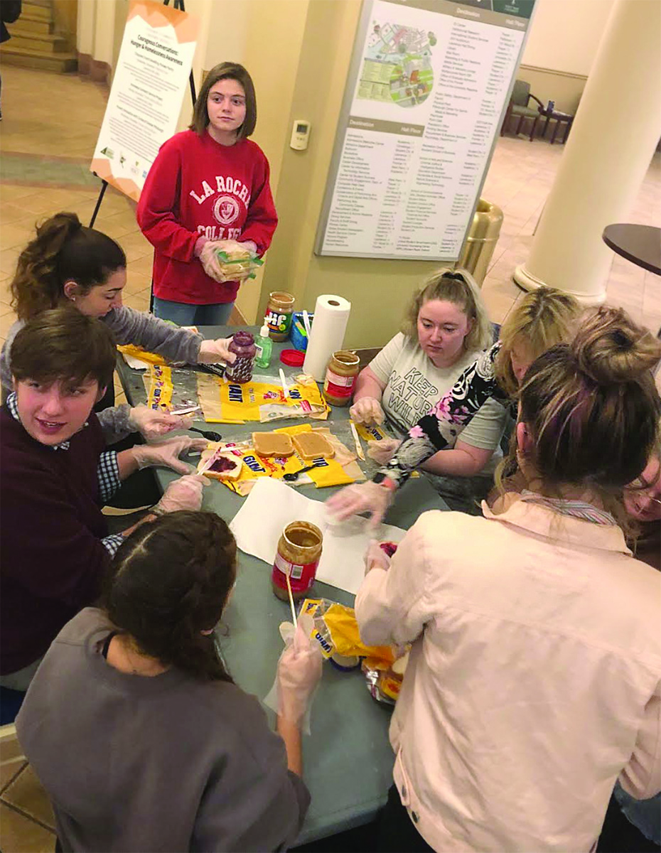 """Students gather in the Lawrence Hall lobby to make sandwiches for the homeless. This """"simple act of kindness"""" was presented by the Department of Community Engagement as part of Courageous Conversations: Hunger and Homelessness Awareness."""