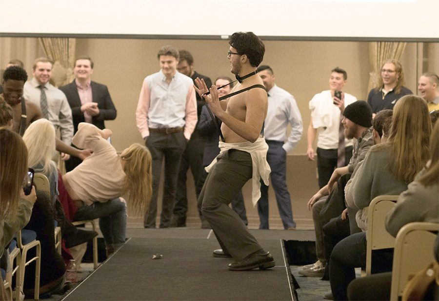 Caleb Gretsky, sophomore cinema production major, dances on the catwalk during the annual Rent-a-Rugger event in the Lawrence Hall Ballroom.
