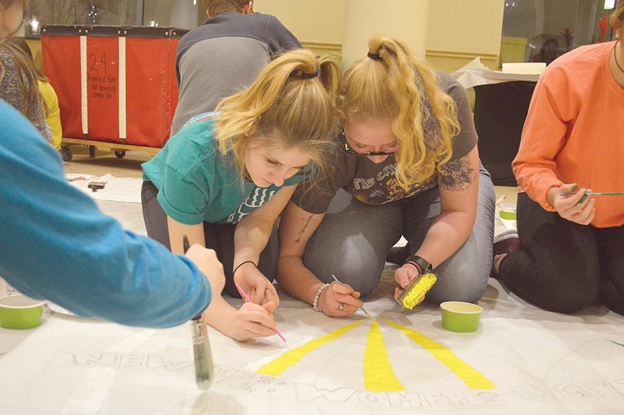 Margaret Hinnebusch, a freshman psychology major, and Cassidy Burke, a freshman theater production major, both members of the Women's Rugby team, paint their mural during the SAIL Showdown on Monday.