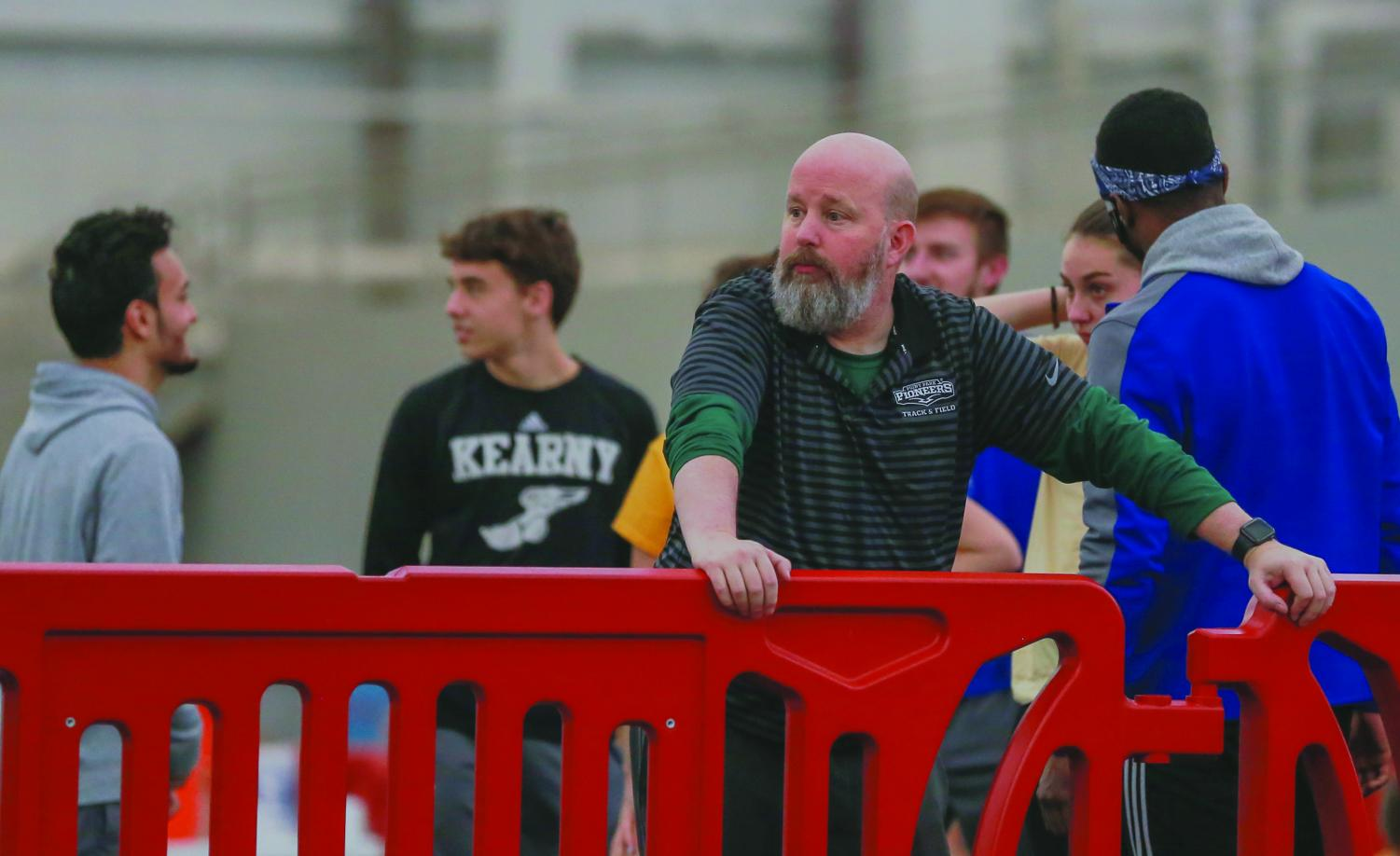 Former head coach of the track and field and cross country teams, Kelly Parsley, stands on the sidelines during a meet earlier this season. Parsley was named Coach of the Year ten times total throughout his tenure with the teams before his termination on Friday.