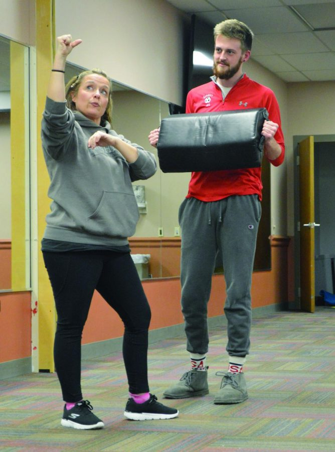 """Greg Nolf, a junior secondary education major, holds a strike shield as Krav Maga specialist Kathy Kluk demonstrates self-defense methods for Future Educators of America members in the Student Center Tuesday evening. """"The number one thing is awareness and number two is feeling empowered,"""" Kluk said."""