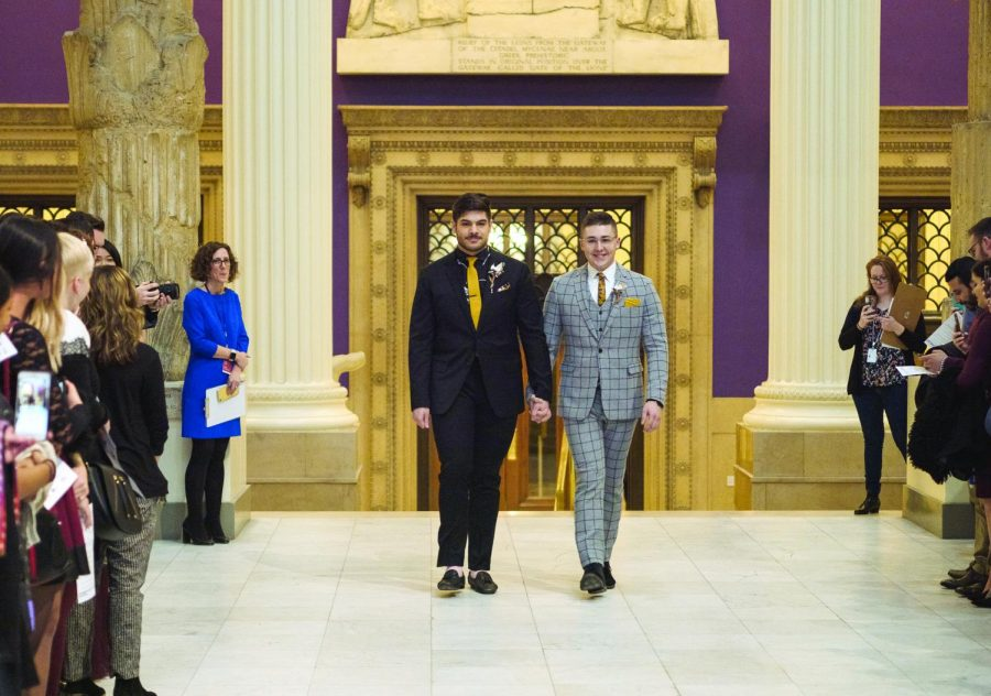 """Louis Spanos (left) and Colten Gill (right) walk down the """"aisle"""" at the Carnegie Museum of Art."""