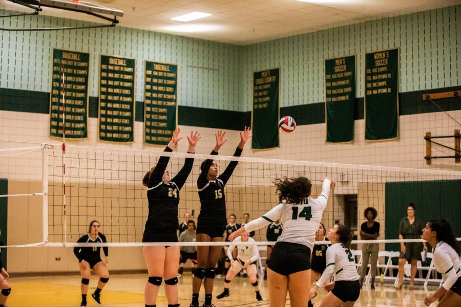 Freshman Taylor Small (left) and junior Jazlyn Rozier (right) go up to block a ball against Salem University in their home opener.