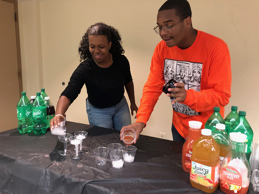 BSU members Divine Kennedy and Michael Moran hand out drinks at mixer event in the Lawrence Hall fourth  oor lounge on Sept. 3